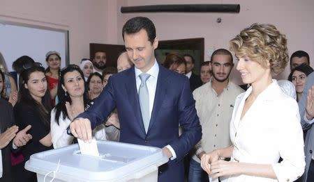 Syria's President Bashar al-Assad and his wife Asma cast their votes in the country's presidential elections at a polling station in Damascus