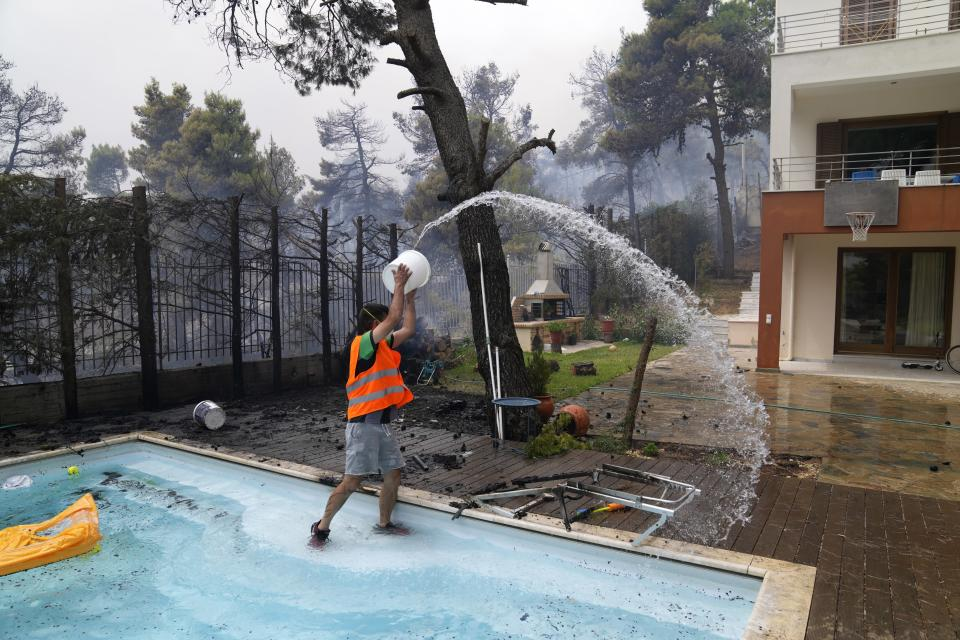 A man throws water from a swimming pool as the fire approaches his house in Ippokratios Politia village, about 35 kilometres (21 miles) north of Athens, Greece, Friday, Aug. 6, 2021. Thousands of people fled wildfires burning out of control in Greece and Turkey on Friday, as a protracted heat wave turned forests into tinderboxes and flames threatened populated areas, electricity installations and historic sites. (AP Photo/Thanassis Stavrakis)