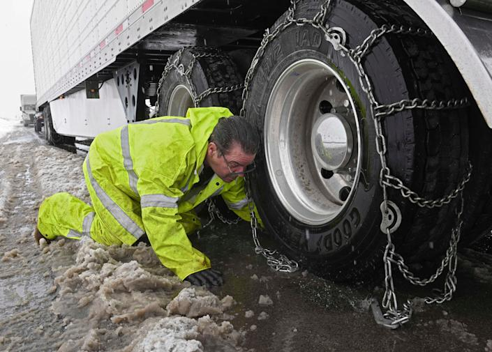 Truck driver Russel Daily pulls over on the west bound I-80 just outside of Reno, Nev. to install chains on his semi-trailer trucks on Thursday, Jan. 28, 2021. An atmospheric river storm pumped drenching rains into the heart of California on Thursday as blizzard conditions buried the Sierra Nevada in snow. (Andy Barron/Reno Gazete-Journal via AP) ORG XMIT: NVREN404