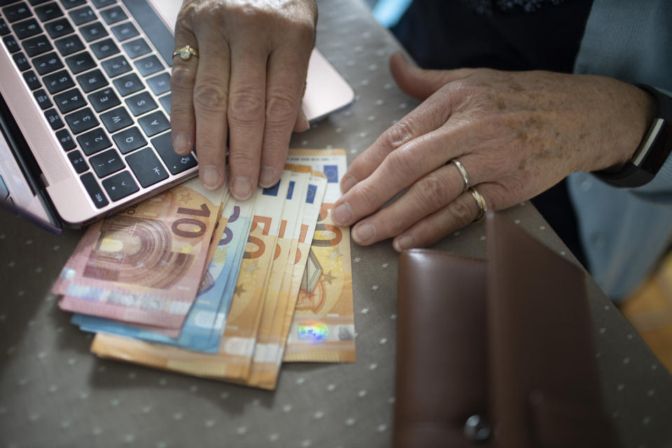 RADEVORMWALD, GERMANY - MAY 12:  In this photo illustration you find cash next to an laptop and the hands of an old woman on May 12, 2020 in Radevormwald, Germany. (Photo by Ute Grabowsky/Photothek via Getty Images)