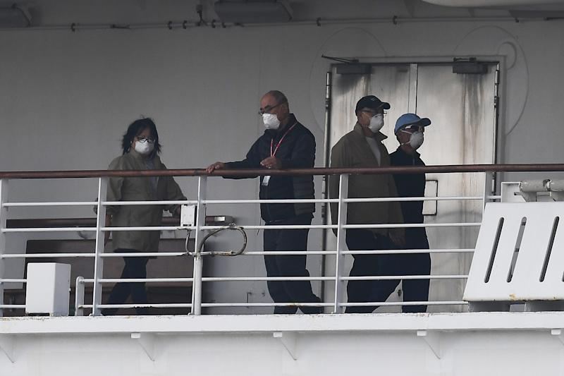 Passengers are seen on the deck of the Diamond Princess cruise ship, with around 3,600 people quarantined onboard due to fears of the new coronavirus, at the Daikoku Pier Cruise Terminal in Yokohama port on February 14, 2020. - The death toll from China's coronavirus epidemic neared 1,500 on February 14 as the United States complained of a lack of transparency from Beijing over its handling of a crisis that has fuelled global panic. (Photo by CHARLY TRIBALLEAU / AFP) (Photo by CHARLY TRIBALLEAU/AFP via Getty Images)