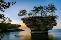 """<p>This fascinating rock formation off the coast of Port Austin, Michigan, came to be after many years of waves wore down the stone. The land surrounding <a href=""""http://huroncountyparks.com/blog/about-turnip-rock-in-port-austin"""" rel=""""nofollow noopener"""" target=""""_blank"""" data-ylk=""""slk:Turnip Rock"""" class=""""link rapid-noclick-resp"""">Turnip Rock</a> is privately owned, however, so the only way to get up close and personal with the island is via water. Note that the area is especially shallow, so <a href=""""http://www.portaustinkayak.com/turnip-rock/"""" rel=""""nofollow noopener"""" target=""""_blank"""" data-ylk=""""slk:stepping out of a kayak"""" class=""""link rapid-noclick-resp"""">stepping out of a kayak</a> to take a beautiful photo like this one is doable.</p>"""