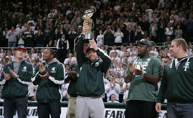 Michigan State football player Kyler Elsworth holds the 100th Rose Bowl championship trophy as he stands with players Connor Cook, from left, Bennie Fowler, Micajah Reynolds and Jack Allen during halftime at an NCAA college basketball game between Michigan State and Ohio State, Tuesday, Jan. 7, 2014, in East Lansing, Mich. (AP Photo/Al Goldis)