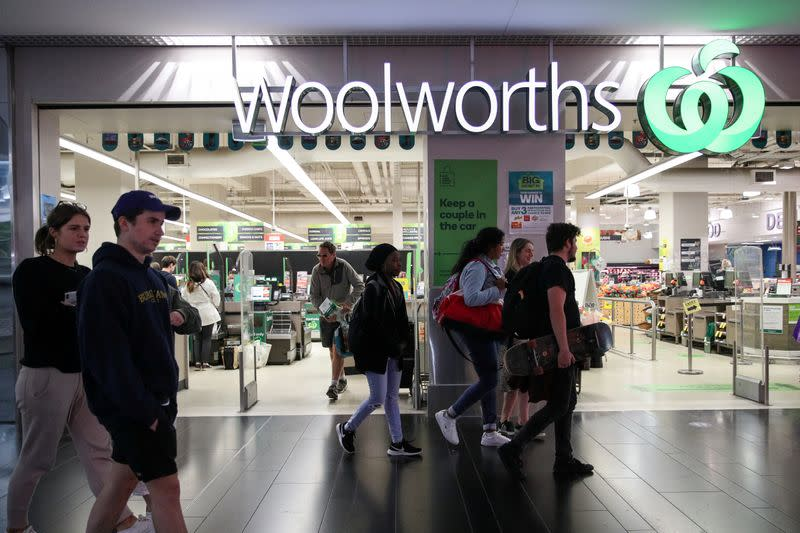 FILE PHOTO: People walk past a Woolworths supermarket in Sydney