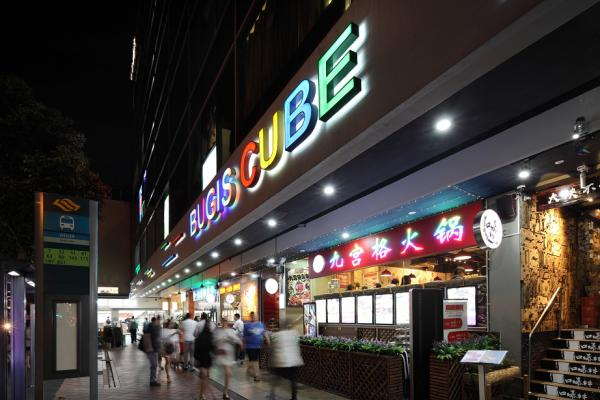 Pedestrians walking past the restaurants on the ground floor of Bugis Cube.