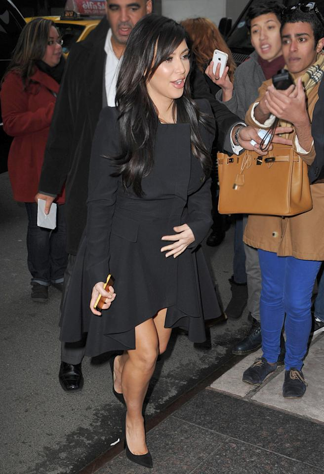 Pregnant Kim Kardashian hides her growing bump under a black dress while out in New York.