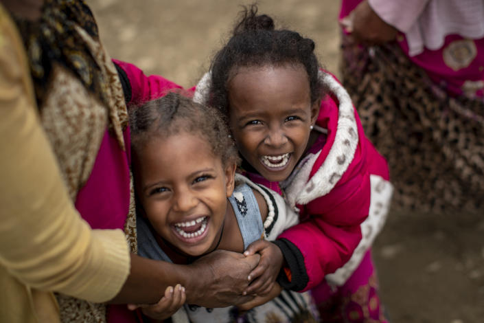 Two displaced Tigrayan girls giggle next to their mother, left, as their photograph is taken outside the Hadnet General Secondary School which has become a makeshift home to thousands displaced by the conflict, in Mekele, in the Tigray region of northern Ethiopia Wednesday, May 5, 2021. The Tigray conflict has displaced more than 1 million people, the International Organization for Migration reported in April, and the numbers continue to rise. (AP Photo/Ben Curtis)