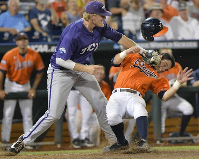 TCU first baseman Kevin Cron, left, tags out Virginia's Kenny Towns who was caught in a run down between third base and home plate in the eighth inning of an NCAA baseball College World Series game in Omaha, Neb., Tuesday, June 17, 2014. (AP Photo/Ted Kirk)