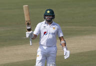 Pakistan's batsman Azhar Ali raises bat to celebrate his fifty during the second day of the first cricket test match between Pakistan and South Africa at the National Stadium in Karachi, Pakistan, Wednesday, Jan. 27, 2021. (AP Photo/Anjum Naveed)