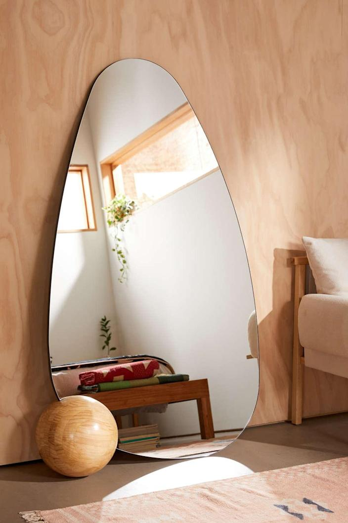 """We always love an unconventionally shaped mirror, and this one is beyond cool. The rounded teardrop shape of the frameless mirror is accented by a spherical wooden mount that adds a funky asymmetry we can't get enough of. $429, Urban Outfitters. <a href=""""https://www.urbanoutfitters.com/shop/safi-floor-mirror?color=020&type=REGULAR&size=ONE%20SIZE&quantity=1"""" rel=""""nofollow noopener"""" target=""""_blank"""" data-ylk=""""slk:Get it now!"""" class=""""link rapid-noclick-resp"""">Get it now!</a>"""