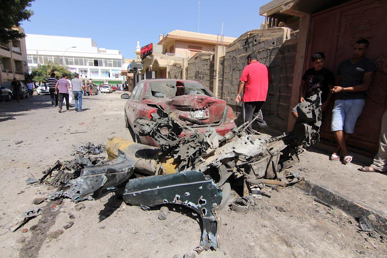 Civilians gather at the site where a car bomb went off outside the building housing Swedish and Finnish consulates on Friday, Oct. 11, 2013 in Libya's eastern city of Benghazi, badly damaging the building, but leaving no casualties. Benghazi has been hit by a wave of attacks against government offices and targeted killings in recent months as security agencies struggle to secure Libya since the 2011 civil war. Weapons have proliferated and a number of militias have vied for authority, operating with impunity.(AP Photo/Mohammed el-Shaiky)