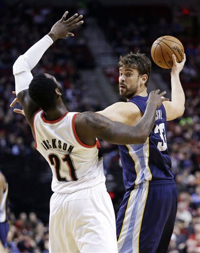 Memphis Grizzlies center Marc Gasol, right, of Spain, looks to pass as he holds off Portland Trail Blazers center J.J. Hickson during the first quarter of an NBA basketball game in Portland, Ore., Tuesday, March 12, 2013. (AP Photo/Don Ryan)