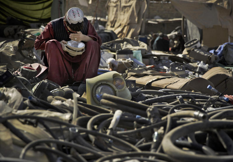 FILE-In this file picture taken Nov. 2, 2013 photo an Afghan scrap dealer checks to see if a head light bought as junk from the U.S. military is working at a junk yard in Kandahar, southern Afghanistan. As the United States military packs up to leave Afghanistan, ending 13 years of war, it is looking to sell or dispose of billions of dollars in military hardware, including its sophisticated and highly specialized mine resistant vehicles, but finding a buyer is complicated in a region where relations between neighboring countries are mired in suspicion and outright hostility.(AP Photo/Anja Niedringhaus, file)
