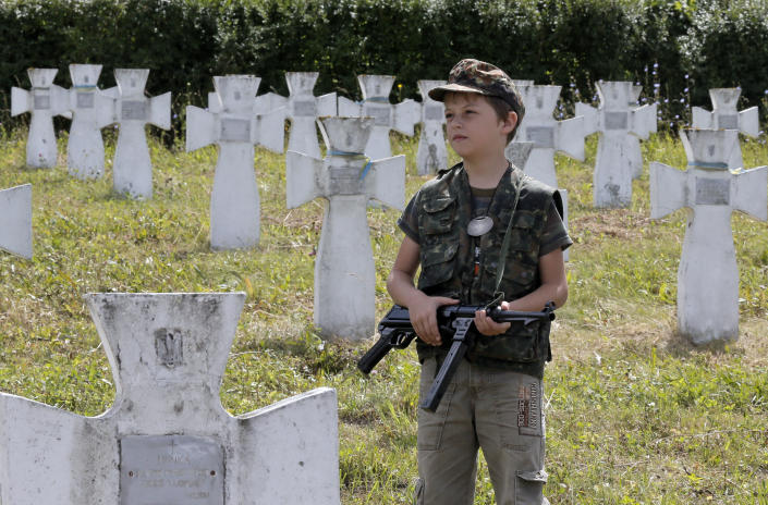 A boy with a toy gun stands near the graves in the SS Galician Division cemetery near the village of Chervone in western Ukraine on Sunday, July 21, 2013. Western Ukraine marked the 70th anniversary of creation of the SS Galician Division. (AP Photo/Efrem Lukatsky)