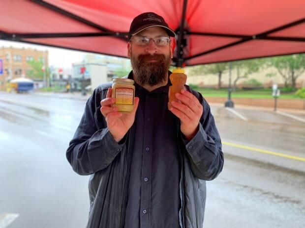 Scott Mullen, who sells honey at the outdoor market with his mom, says he's hoping the outdoor Downtown Charlottetown Farmers' Market gets busier when P.E.I. opens to the rest of Canada. (Tony Davis/CBC - image credit)