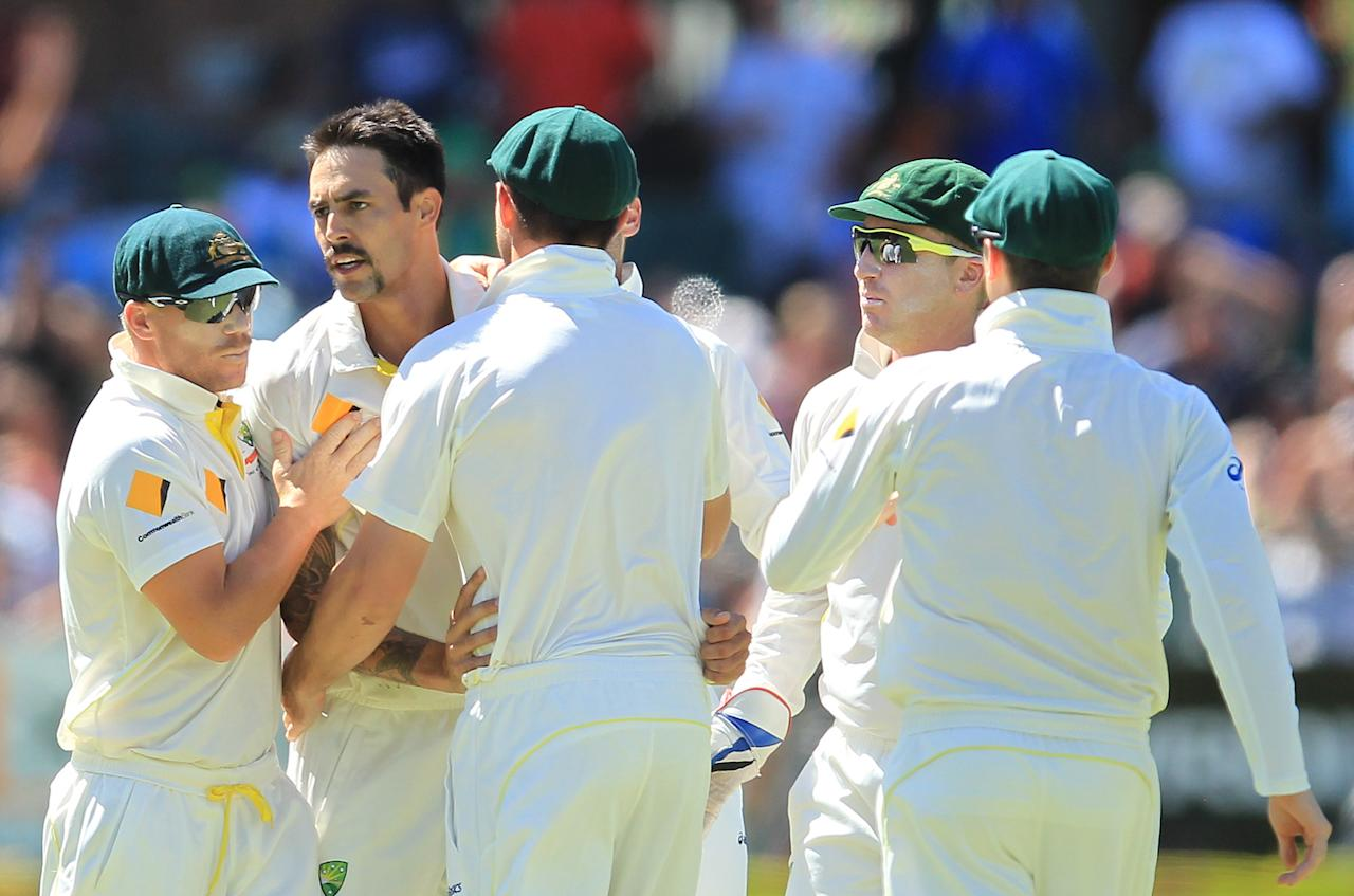 Australia's bowler Mitchell Johnson, second from left, celebrates with teammates after bowling South Africa's captain Graeme Smith, for 14 runs on the third day of their 2nd cricket test match, at St George's Park in Port Elizabeth, South Africa, Saturday, Feb. 22, 2014. (AP Photo/ Themba Hadebe)