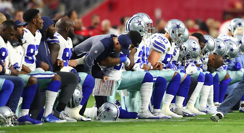 Dallas Cowboys players kneel together with their arms locked prior to the game against the Arizona Cardinals at University of Phoenix Stadium on Monday.
