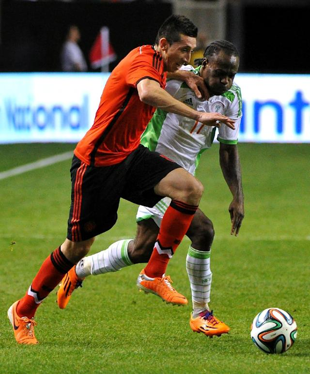 Mexico's Hector Herrera, left, and Nigeria's Victor Moses (11) race for the ball during the first half of an international friendly soccer match Wednesday, March 5, 2014, in Atlanta. (AP Photo/David Tulis)