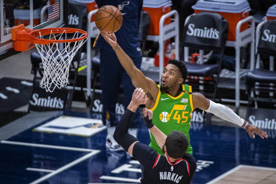 Utah Jazz guard Donovan Mitchell (45) lays the ball up while guarded by Portland Trail Blazers center Jusuf Nurkic (27) during the first half of an NBA basketball game Thursday, April 8, 2021, in Salt Lake City. (AP Photo/Isaac Hale)