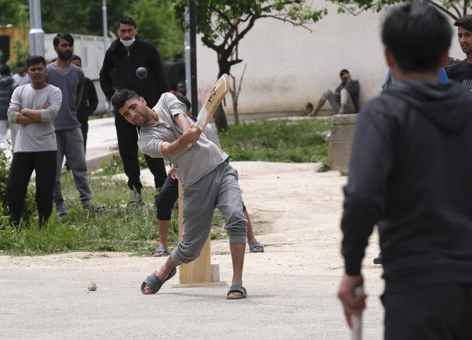A batter hits the ball as migrants play a game of cricket in Blazuj migrant camp in Bosnia's capital of Sarajevo Wednesday, May 19, 2021. Thanks to a Rome-based humanitarian group, migrants stranded at camps in Bosnia were able to forget their everyday difficulties and enjoy cricket. The Baobab Experience group has brought cricket equipment for the migrants in the Bosnian capital of Sarajevo and the central town of Tuzla, offering a rare opportunity for relaxation and fun for the people who spend months, if not years, stuck in camps while fleeing war and poverty in their nations and chasing their dreams of a better future. (AP Photo/Kemal Softic)