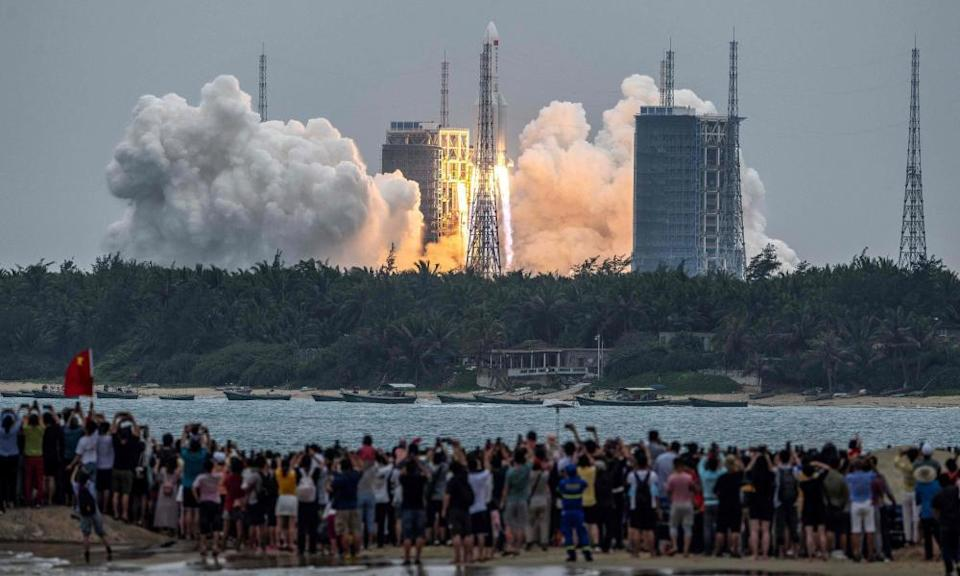 People watch a Long March 5B rocket, carrying China's Tianhe space station core module, as it lifts off from the Wenchang Space Launch Center in southern China's Hainan province. The Pentagon is following the trajectory of the rocket as it is expected to make an uncontrolled entry into the atmosphere this weekend.