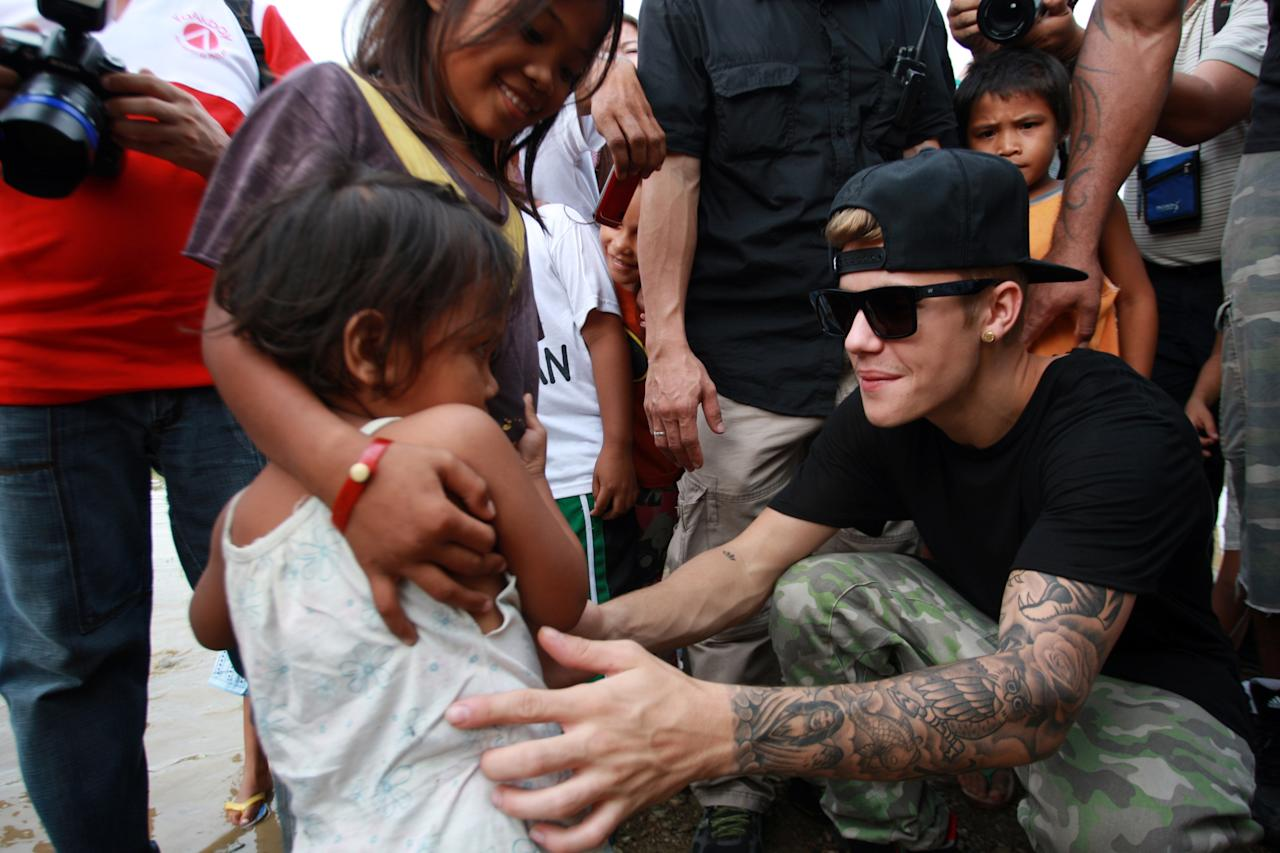 TACLOBAN, LEYTE, PHILIPPINES - DECEMBER 10: Justin Bieber interacts with a young child as he visits San Jose Elementary School on December 10, 2013 in Tacloban, Leyte, Philippines. Bieber previously launched a campaign to help raise money for the victims of super Typhoon Haiyan. Typhoon Haiyan which ripped through Philippines over a month ago has been described as one of the most powerful typhoons ever to hit land, leaving thousands dead and hundreds of thousands homeless. Countries all over the world have pledged relief aid to help support those affected by the typhoon as the relief effort continues. (Photo by Jeoffrey Maitem/Getty Images)