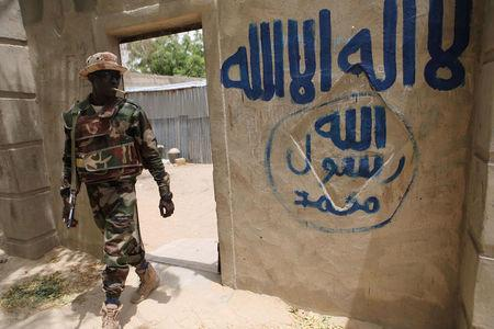 FILE PHOTO: A Nigerien soldier walks out of a house that residents say a Boko Haram militant had forcefully seized and occupied in Damasak