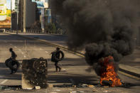 Protesters burn tires to close the main road, after the Lebanese pound hit a record low against the dollar on the black market, in Beirut, Lebanon, Saturday, March 6, 2021. (AP Photo/Hassan Ammar)