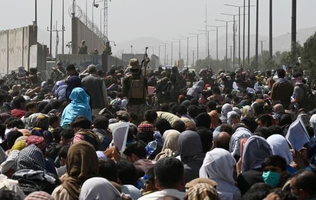 Afghans gather on a roadside near the military part of the Kabul airport on Aug. 20, 2021, hoping to flee from the country after the Taliban's takeover. (Wakil Kohsar/AFP via Getty Images - image credit)