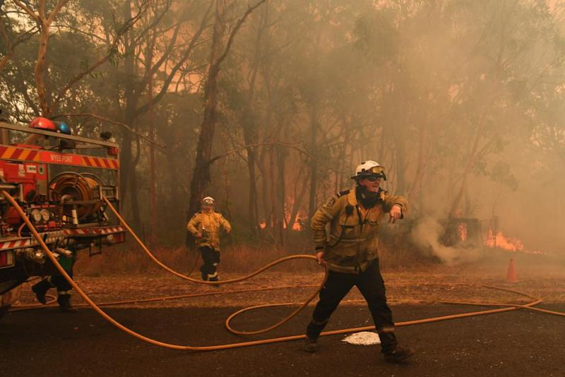 RFS firefighters prepare to fight fire-spotting at the Three Mile Fire on the NSW Central Coast on Tuesday.