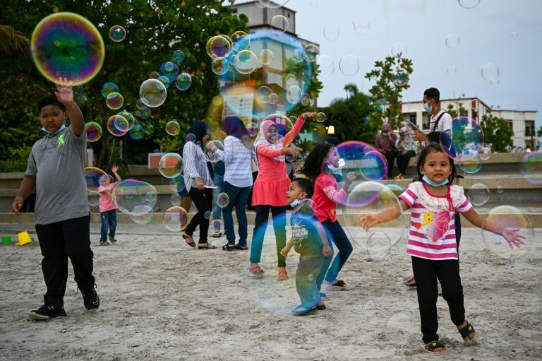 Children play in Pantai Cenang on Langkawi a day before the Malaysian holiday island reopened to domestic tourists (AFP/Mohd RASFAN)
