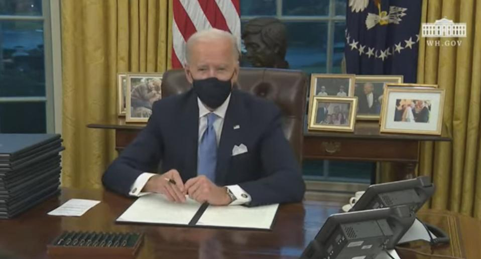 US President Joe Biden sits in his office and signs executive orders.