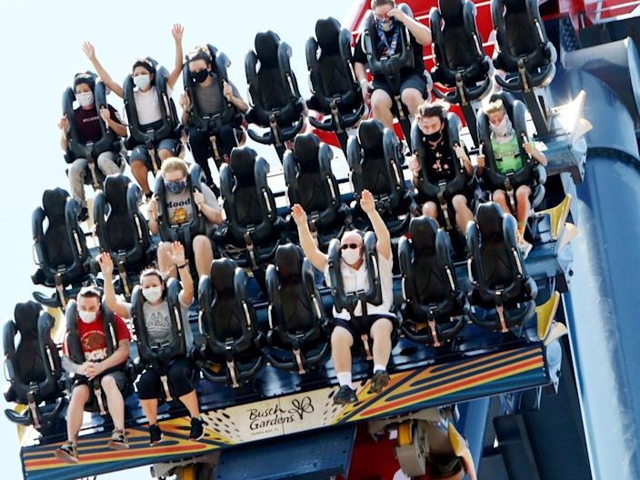 Patrons of Busch Gardens Tampa Bay enjoy the 200-foot dive on the SheiKra roller coaster, Thursday, June 11, 2020, in Tampa. The park, owned and operated by SeaWorld Entertainment, has reopened to the public for the first time in almost 3 months after closing on March 16 because of the coronavirus pandemic. (Douglas R. Clifford/Tampa Bay Times via AP)
