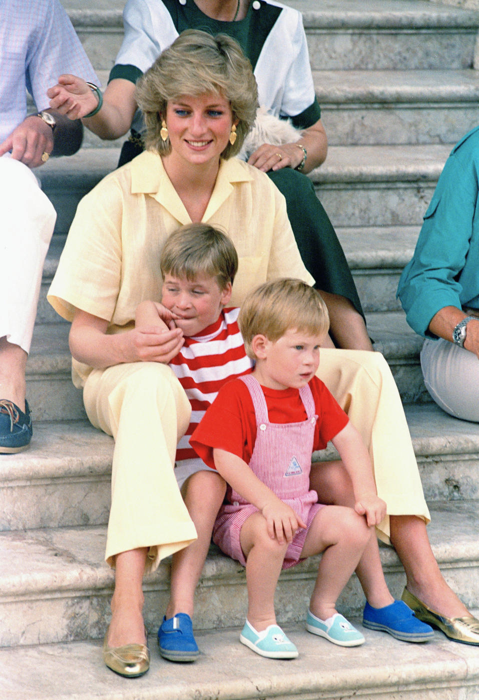"""FILE - In this Aug. 9, 1987 file photo, Britain's Princess Diana of Wales smiles as she sits with her sons, Princes Harry, foreground, and William, on the steps of the Royal Palace on the island of Mallorca, Spain. For someone who began her life in the spotlight as """"Shy Di,"""" Princess Diana became an unlikely, revolutionary during her years in the House of Windsor. She helped modernize the monarchy by making it more personal, changing the way the royal family related to people. By interacting more intimately with the public -- kneeling to the level of children, sitting on edge of a patient's hospital bed, writing personal notes to her fans -- she set an example that has been followed by other royals as the monarchy worked to become more human and remain relevant in the 21st century. (AP Photo/John Redman, File)"""