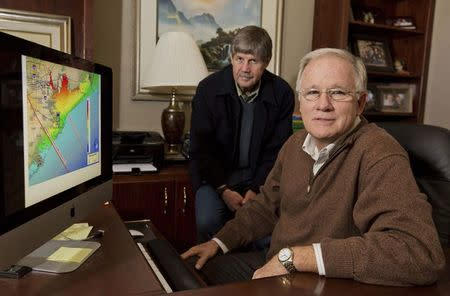 Jim Blackburn (L), professor of Environmental Law, and Philip Bedient (R), professor of Civil and Environmental Engineering at the Rice University School of Engineering; pose next to Houston-Galveston coastal map displayed on a computer screen at the school in Houston, Texas November 21, 2014. REUTERS/Richard Carson