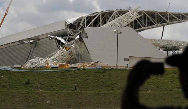 """A man takes a picture of a crane that collapsed on the site of the Arena Sao Paulo stadium, known as """"Itaquerao"""", which will host the opening soccer match of the 2014 World Cup, in Sao Paulo"""