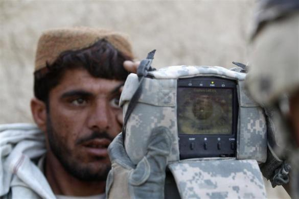 A U.S. Army soldier from 4-73 Cavalry Regiment, 82nd Airborne Division carries out an identification check on an Afghan man with a biometric device during a mission in Zhary district of Kandahar province, southern Afghanistan April 18, 2012.