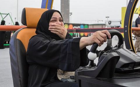 Saudi woman uses a driving simulator at an event to promote the lifting of Saudi Arabia's women's driving ban - Credit: Sam Tarling for The Telegraph