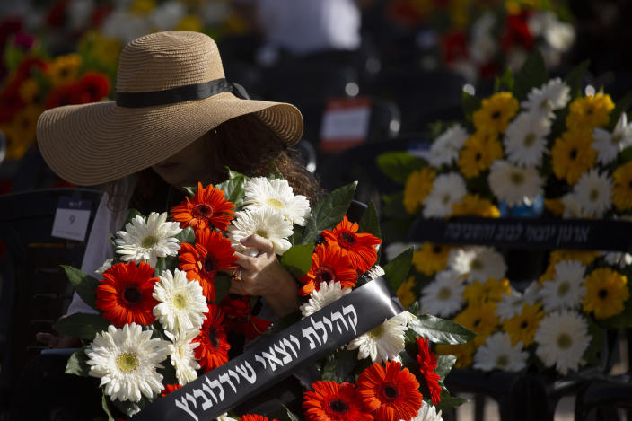A woman holds a wreath at a ceremony marking the annual Holocaust Remembrance Day, at Yad Vashem Holocaust Memorial in Jerusalem, Thursday, April 8, 2021. (AP Photo/Maya Alleruzzo, Pool)