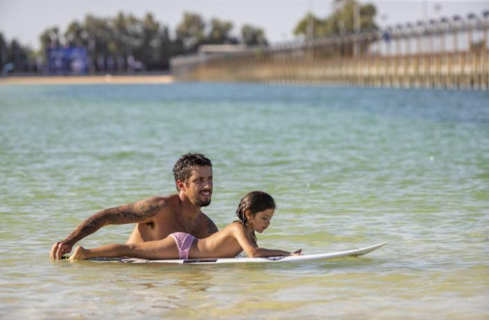 Filipe Toledo, of Brazil celebrates by pushing his child around of his surfboard on Father's Day