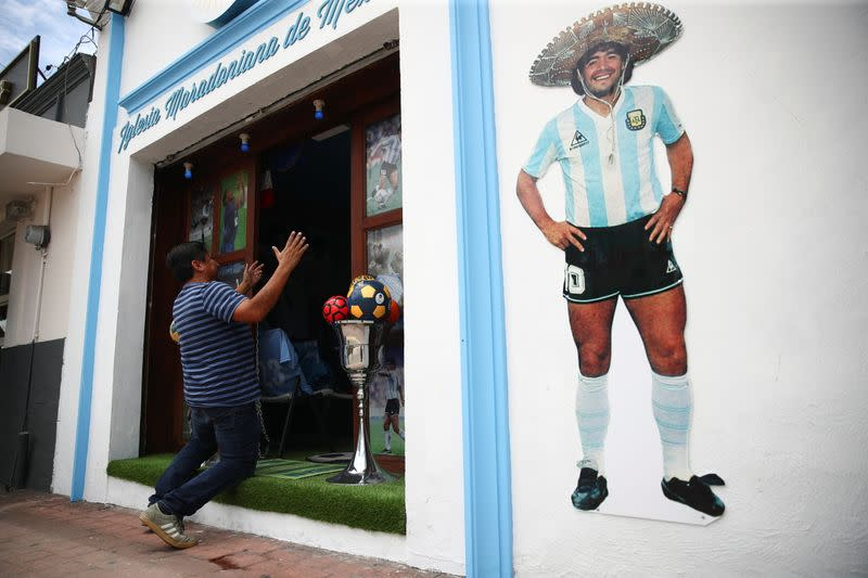 A fan kneels at the entrance to the first Mexico's church in memory of soccer legend Diego Armando Maradona in San Andres Cholula