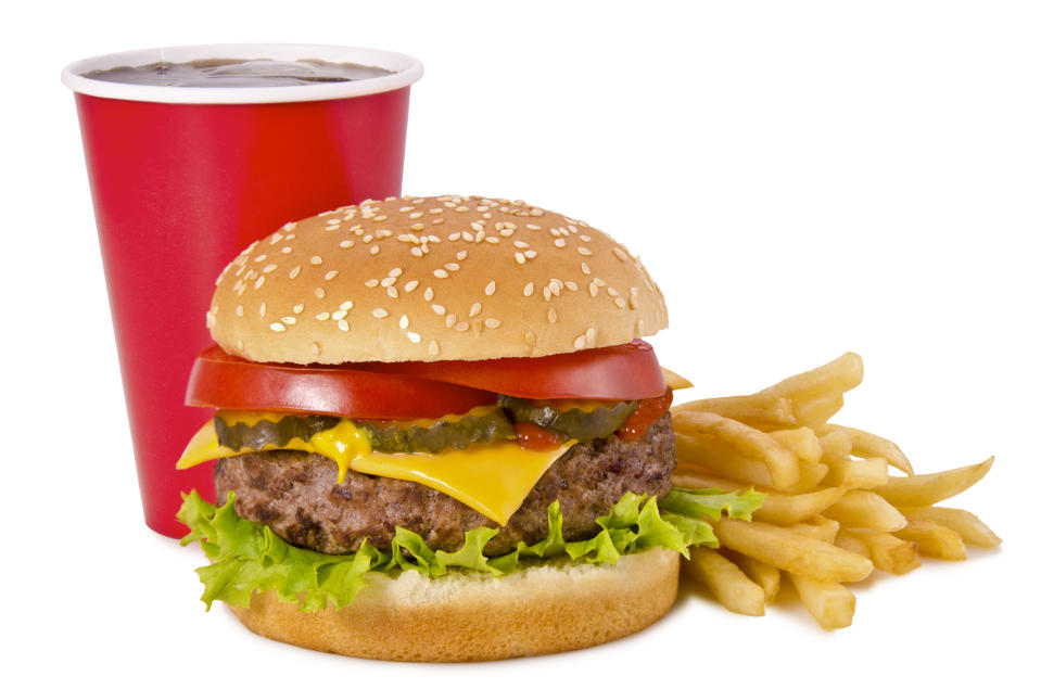 Cheeseburger, french fries and cola on a white background. Front view.