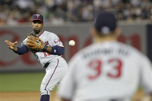 Minnesota Twins second baseman Alexi Casilla throws out New York Yankees' Mark Teixeira at first base to end the third inning of a baseball game at Yankee Stadium in New York, Monday, April 16, 2012. (AP Photo/Seth Wenig)
