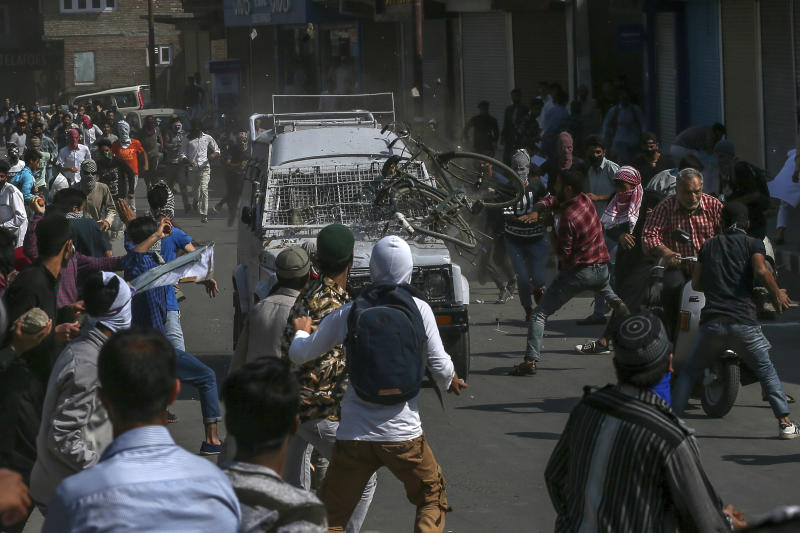 Kashmiri Protesters throw rocks, bricks and a cycle on an Indian paramilitary vehicle in Srinagar, Indian controlled Kashmir, Friday, June 1, 2018. Three people were injured, one of them seriously, after they were hit and run over by the vehicle. (AP Photo/Dar Yasin)