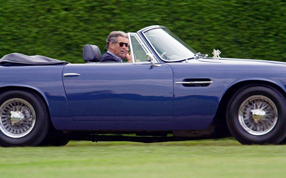 Prince Charles driving His Aston Martin DB5 Volante convertible at Cirencester Park Polo Club - Tim Graham/Getty Images