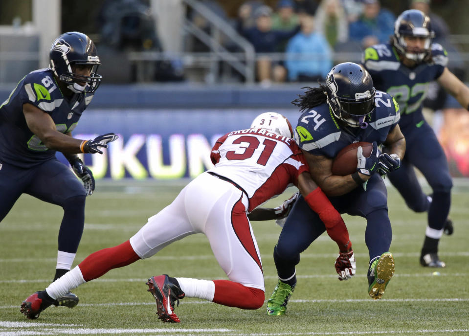 Seattle Seahawks running back Marshawn Lynch (24) rushes against Arizona Cardinals cornerback Antonio Cromartie (31) in the second half of an NFL football game, Sunday, Nov. 23, 2014, in Seattle. (AP Photo/Elaine Thompson)