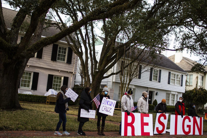 "Demonstrators stand in front of U.S. Senator Ted Cruz's home demanding his resignation, Thursday, Feb. 18, 2021, in Houston. Cruz has acknowledged that his family vacation to Mexico was ""obviously a mistake"" as he returned stateside following an uproar over his disappearance during a deadly winter storm."