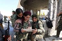 Female fighters from the Democratic Forces of Syria use a tablet in al-Shadadi town, in Hasaka province, Syria February 26, 2016. REUTERS/Rodi Said