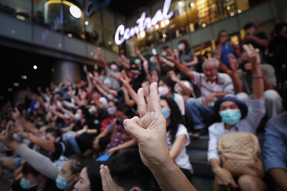 Pro-democracy demonstrators flash a three-finger salute of defiance during a protest rally at the Silom business district in Bangkok, Thailand, Thursday, Oct. 29, 2020. The protesters continue to gather Thursday with their three main demands of Prime Minister Prayuth Chan-ocha's resignation, changes to a constitution that was drafted under military rule and reforms to the constitutional monarchy. (AP Photo/Sakchai Lalit)