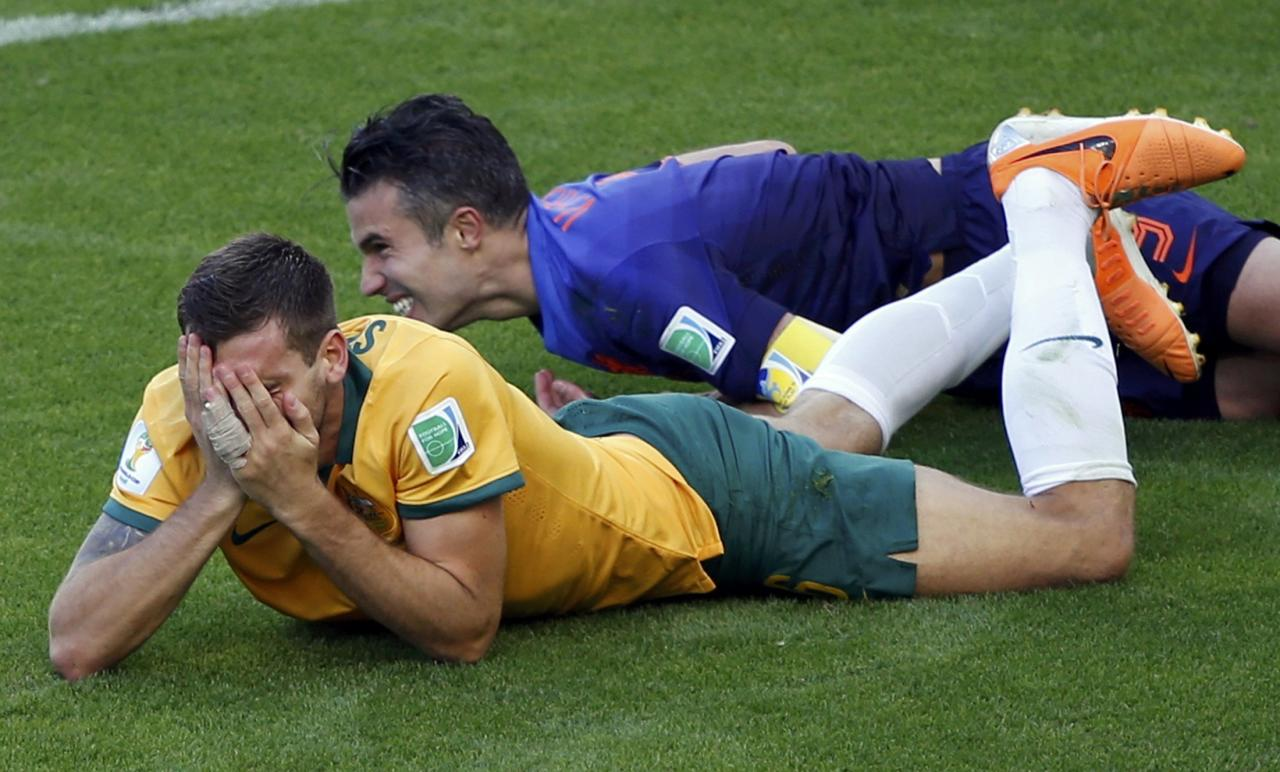 Australia's Matthew Spiranovic (L) covers his face in pain after being fouled by Robin van Persie of the Netherlands during their 2014 World Cup Group B soccer match at the Beira Rio stadium in Porto Alegre June 18, 2014. REUTERS/Marko Djurica (BRAZIL - Tags: SOCCER SPORT WORLD CUP)